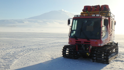 A PistenBully sits on the sea ice with Mt. Erebus in the distance. Turtle Rock, Antarctica. Photo by Timothy R. Dwyer.