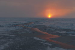 A sunset reflected in a newly-frozen lead in the sea ice. Aboard the USCGC Healy at the Alpha Ridge in the Arctic Ocean. Photo by Bill Schmoker.