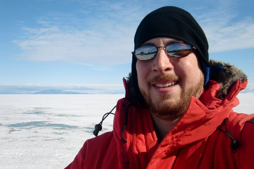 Selfie photograph taken at Hut Point.  In the background across the Ross Ice Shelf is Mt. Discovery (far left, and partly hidden by clouds) with the hills of Brown Peninsula.