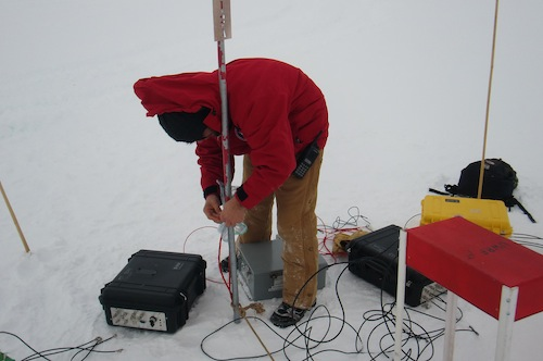 Sam checking up the data acquisition modules (DAQs) above an IceTop tank.