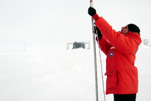 Me taking measurements of accumulated snow above an IceTop tank.