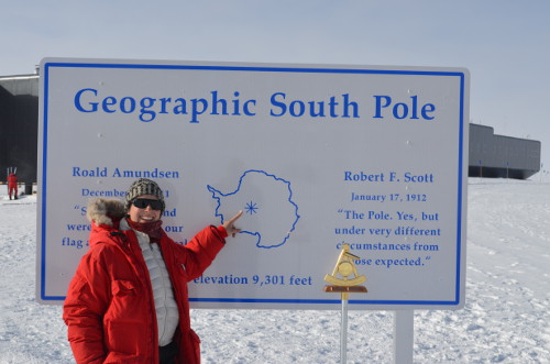 Michelle Brown points to the Geographic South Pole. This is the Geographic South Pole as measured in January of 2011. Amundsen–Scott South Pole Station, Antarctica.  Photo by Andy Stillinger, Courtesy of Michelle Brown (PolarTREC 2011/2012), Courtesy of ARCUS