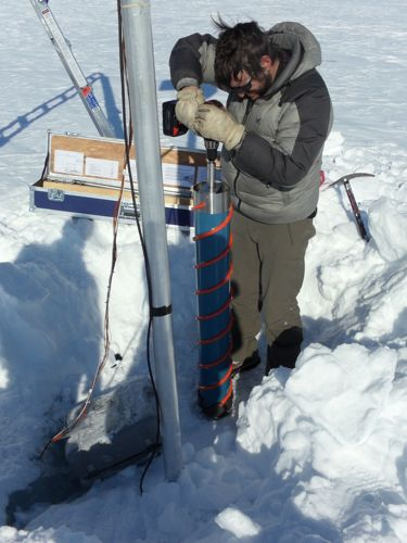 Nikko using ice core drill to make a hole for the new AWS base.