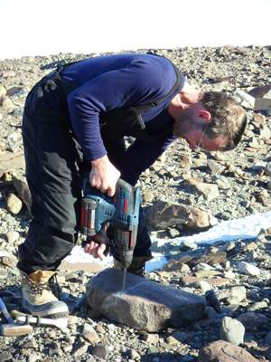 John Stone drilling rock for sampling.