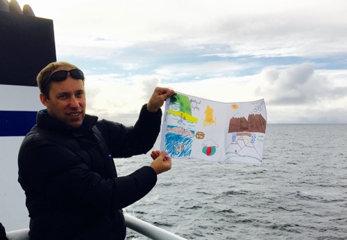 Captain Forest McMullen holds the Arctic organism flag artwork.