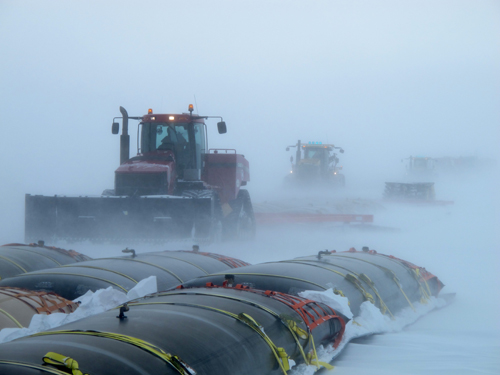 Tractors pulling fuel in a blizzard