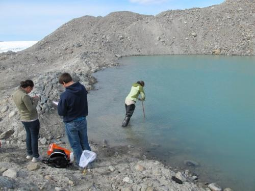 Team chemistry collects water samples at glacial lake.