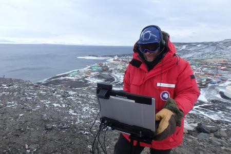 PolarTREC teacher Kevin Dickerson on a Skype call to a classroom in the U.S. from Observation Hill, overlooking McMurdo Station, Antarctica