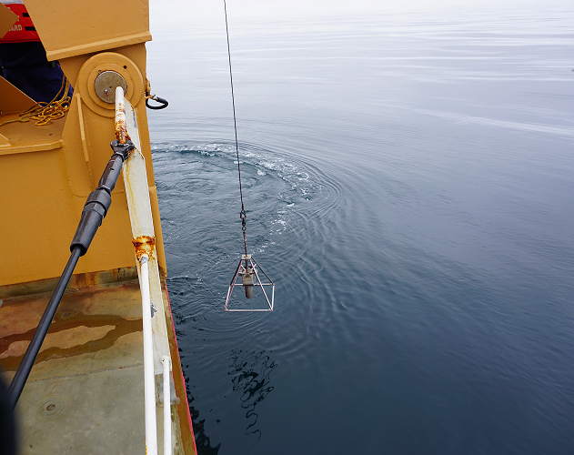 The HAPs core is lowered off the back deck of the USCGC Healy on a calm day in the Chukchi Sea.
