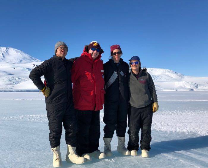 Four people stand on the sea ice in Antarctica