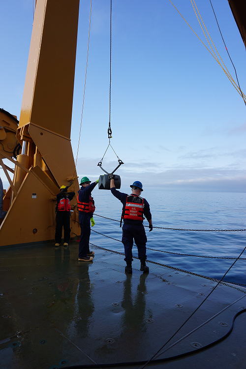 The Coast Guard guiding the van Veen grab off the back of the USCGC Healy.