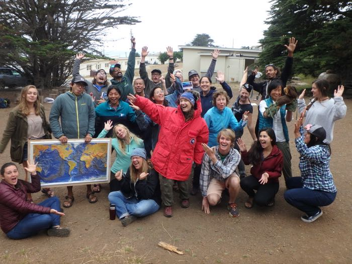 A group of outdoor educators with a map of the world