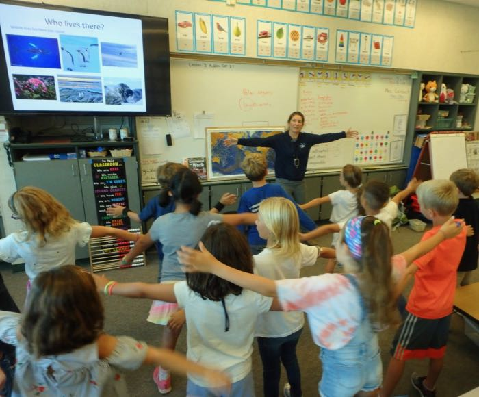A teacher teaches a group of students about the animals that live in Antarctica