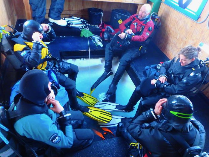 Divers dressed in dry suits sit around a hole in the sea ice