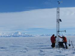 The team raises meteorological instrument equipment onto the Sabrina Automatic Weather Station (AWS), Antarctica.