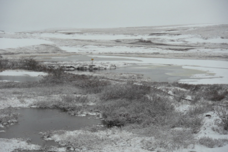 a view across Toolik Lake with fresh snow falling