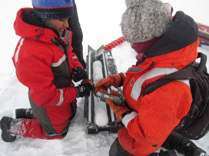 Arthi Ramachandran works on an ice core temperature measurement. On the sea ice near the CCGS Louis S. St-Laurent in the Beaufort Sea. Photo by Dave Jones (PolarTREC 2017), Courtesy of ARCUS.