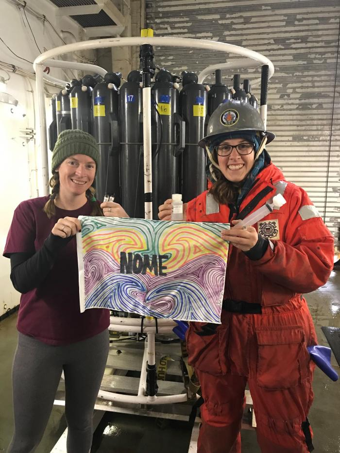 Nicole Villeneuve and Kelly Kapsar holding a flag from the Ecology Explorers program in Nome.