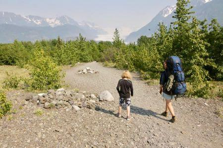 Two people hike on a glacial moraine, surrounded by cottonwood and spruce trees.