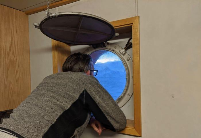 Dr. Ali Graham looks out a porthole on the R/V Nathaniel B. Palmer