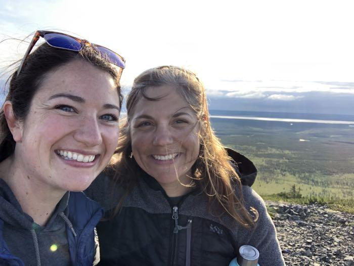 Educator Amanda Ruland and researcher Jennie DeMarco overlooking a boreal forest photographed by Amanda Ruland