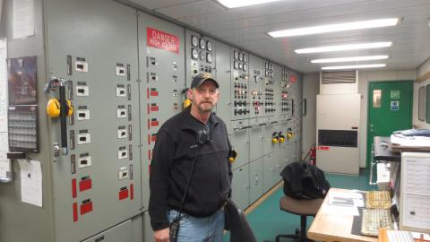 J.P. Pierce, chief engineer in front of the control panel in the engine room.