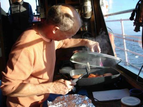 Steve cooking dinner on the Annika Marie.  note the beautiful weather outside.