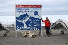 Mr. Wood stands next to the welcome sign for the town of Barrow, Alaska.