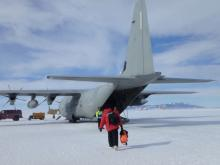 A person walks across the white ice to an airplane.