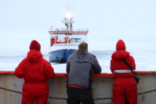 Three people look across the ice to a ship