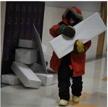 "Student participating in a class project entitled, Polar-ympics, transporting""ice blocks""for construction of an igloo. (Photo by Daphne Lynd.)"