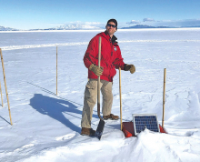 Eric Thuma stands on the McMurdo Ice Sheet, preparing to extract a seismometer. (Photo provided by Dr. Doug MacAyeal)