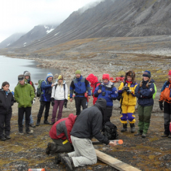 Norwegian group watching a sediment core extrusion.
