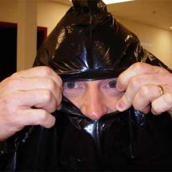 Jeff Peneston emerges from the depths of of his survival garbage bag.