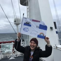 Arctic organism artwork flag from students at the Anvil City Science Academy in Nome Alaska! Celebrity flag holder Jenny Stern! Photo by Lisa Seff.  August 2017.