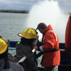 Anvil City Science Academy middle school students work the fire hose on the main deck of the R/V Sikuliaq. Photo by Lisa Seff.  September 18, 2017.
