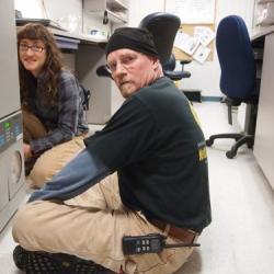 Christina Hammock and Jack Anderson work on a freezer