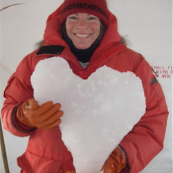 Mindy holding a chunk of heart-shaped ice they pulled out of a dive hole!