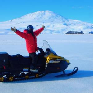 Person with arms raised on a snow machine on the sea ice. A volcanic mountain is in the background.