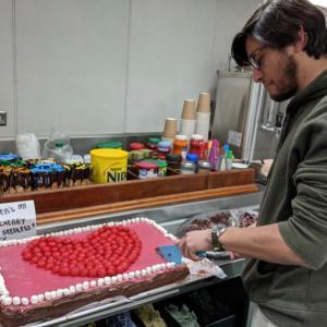 Grad student Santi Muneval cuts a piece of Valentine's Day cake